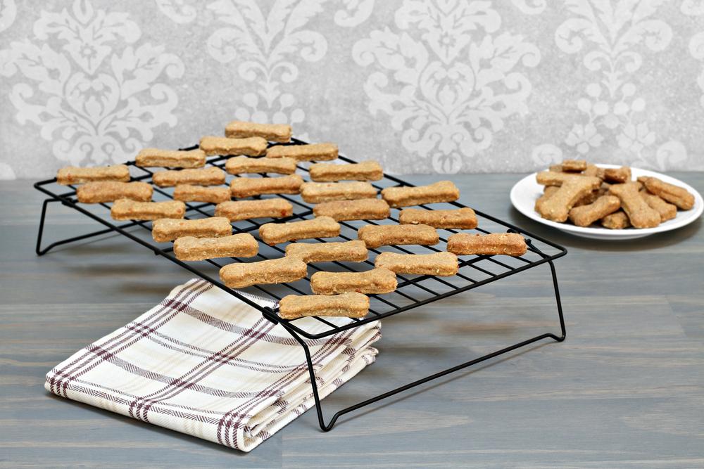 Homemade healthy dog bones cooling on a metal rack.  Selective f